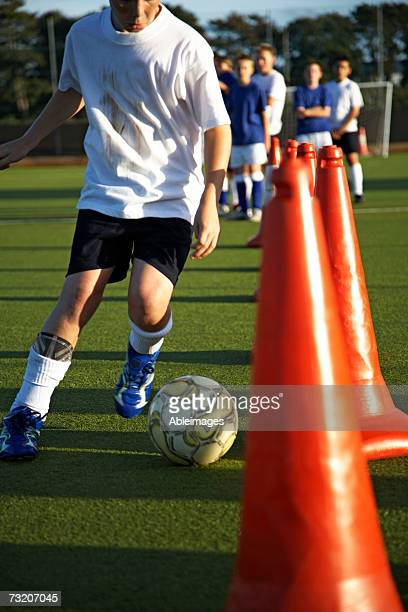 Boys (9-11) dribbling soccer balls around cones on soccer field