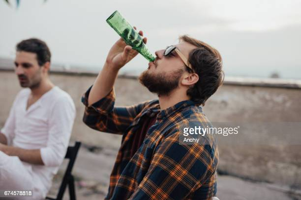 Boys drinking beer and hanging out on the roof
