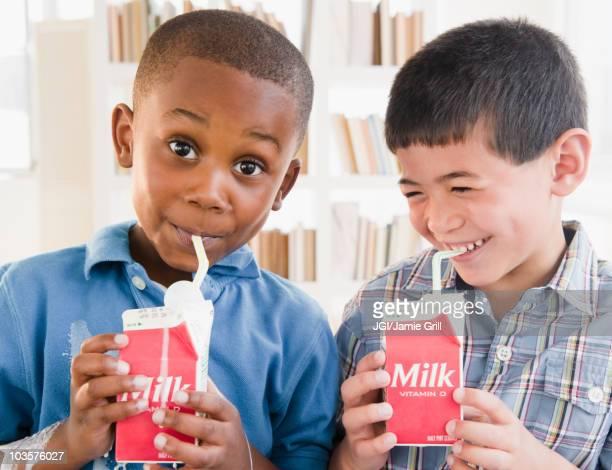 Boys drinking milk from carton