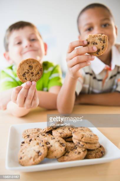 Boys eating chocolate chip cookies