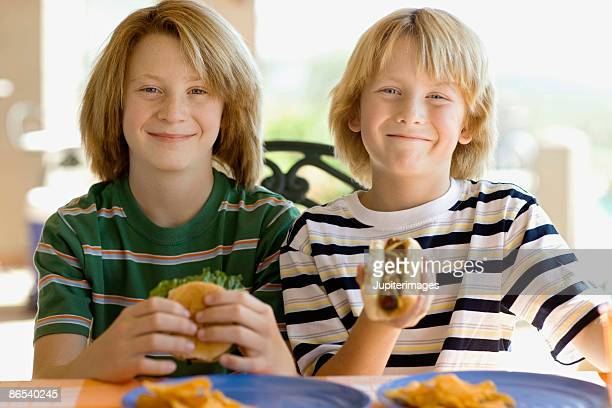 Boys eating hotdog and hamburger