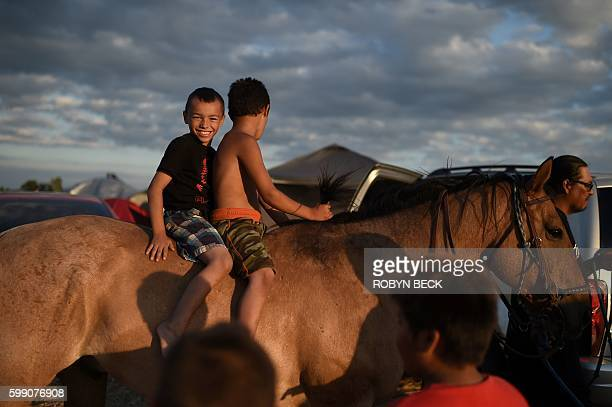 Boys enjoy a later afternoon horseback ride at an encampment where hundreds of people have gathered to join the Standing Rock Sioux Tribe's protest...
