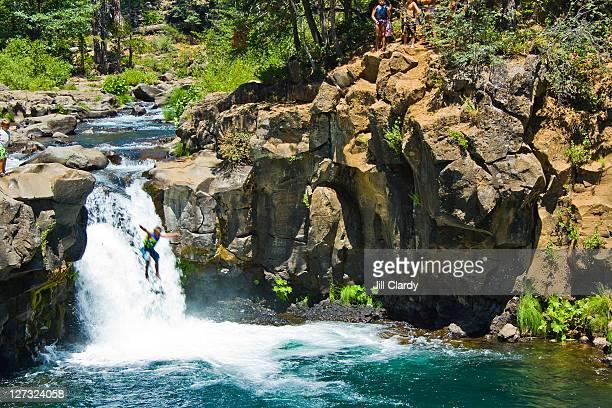 Boys enjoying warm summer jumping into pool