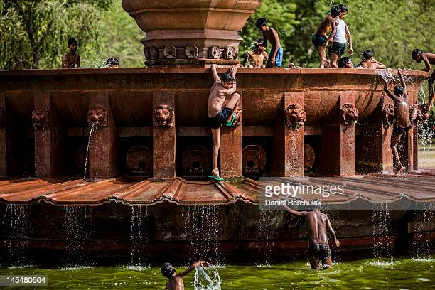 Boys escaping the heat play in a fountain at India Gate monument on May 31 2012 in New Delhi India A Heat wave is continuing across the Northern...