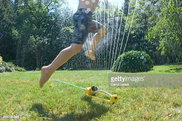 Boy's feet in sprinkler