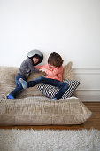 2 boys fighting on a sofa