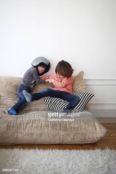 2 boys fighting on a sofa