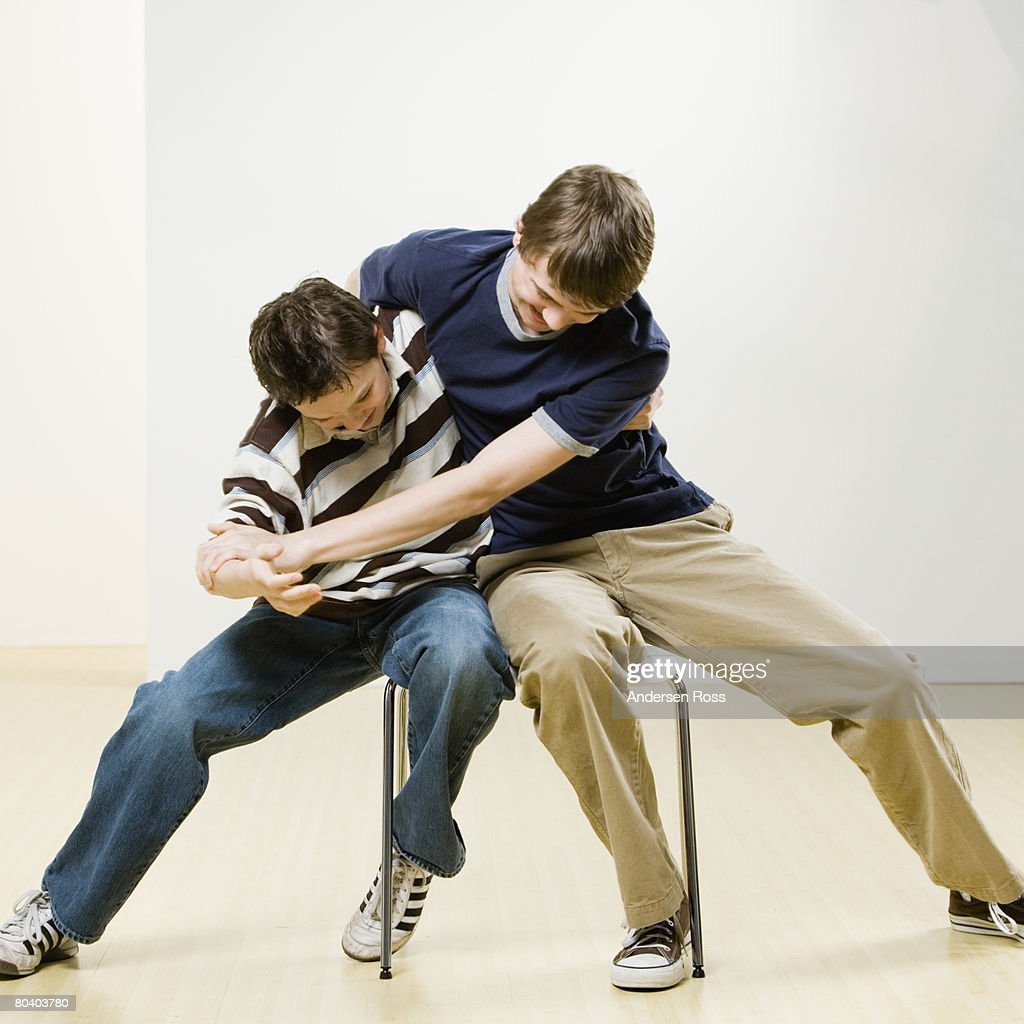 Boys fighting on chair : Stock Photo