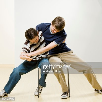 Boys fighting on chair : Foto stock