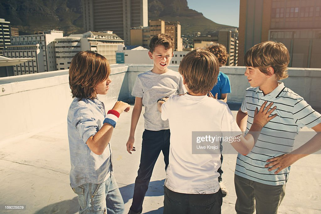 Boys (8 -10 years) fighting on roof top : Stock Photo
