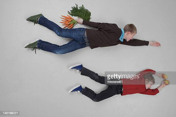 Boys flying with fruit and vegetable