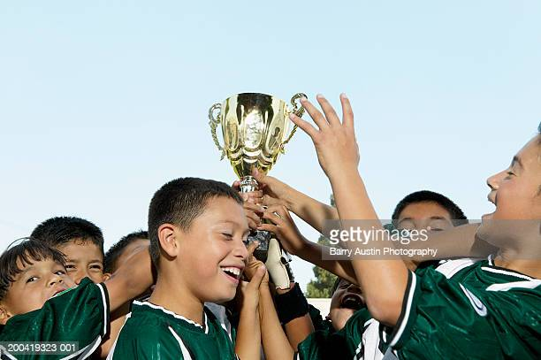 Boys (7-11) football team holding up trophy in celebration, close-up