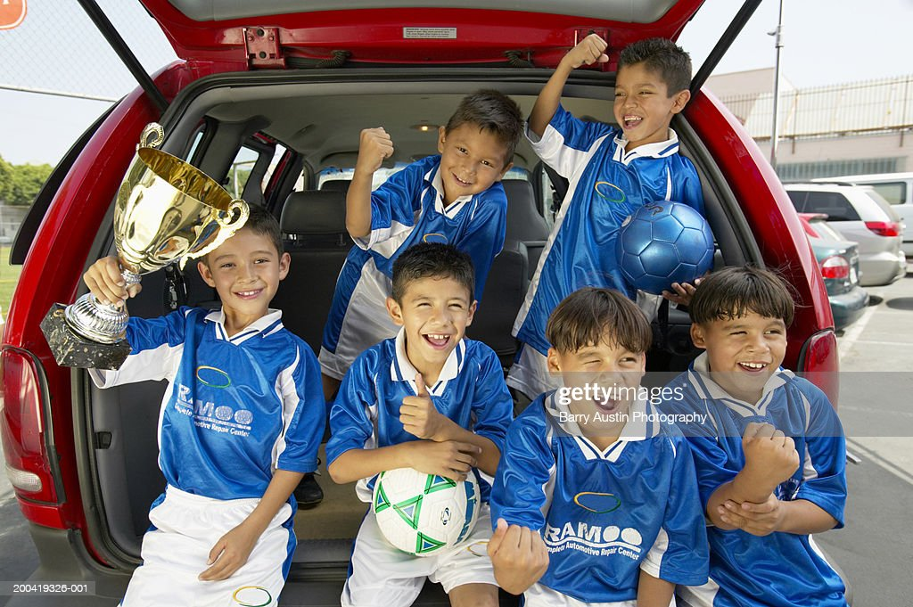Boys (7-11) football team in car boot, holding trophy, smiling