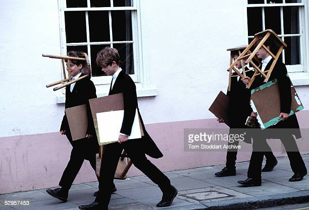 Boys from Eton School carrying stools and art materials set off to sketch scenes along the River Thames at Windsor
