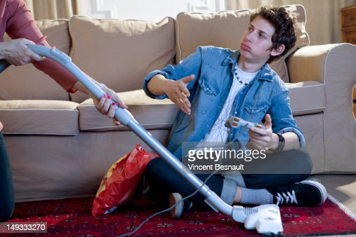 A boy's gaming interrupted by his mum's vacuuming : Stock Photo