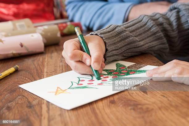 Boys hand drawing christmas tree