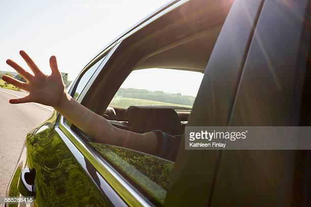 Boys hand outside moving car window