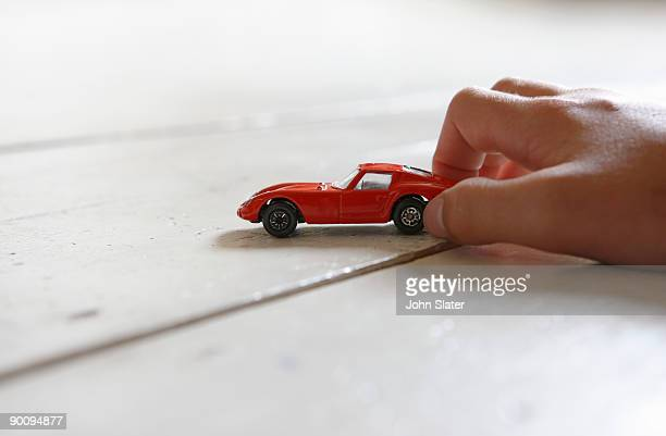 boy's hand playing with toy car on the floor,low a