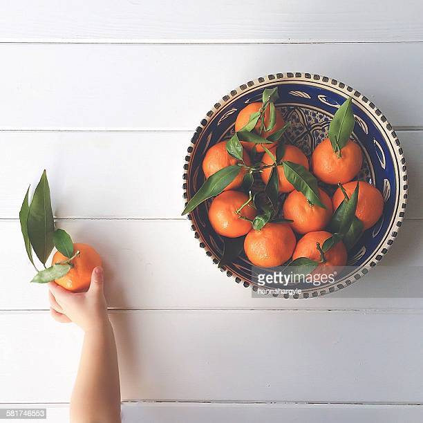 Boy's hand taking a clementine from a bowl