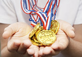 Boys hands held out full of gold medals