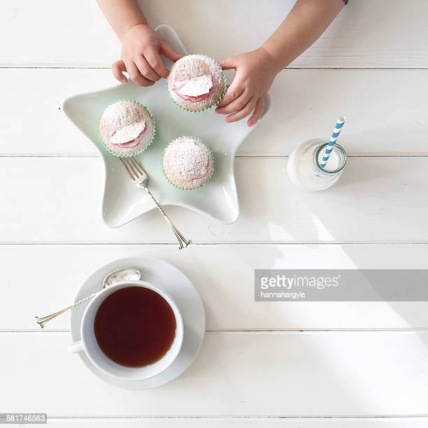Boy's hands taking a cupcake, with tea and bottle of milk