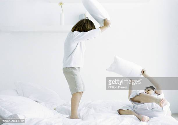 Boys having pillow fight on bed