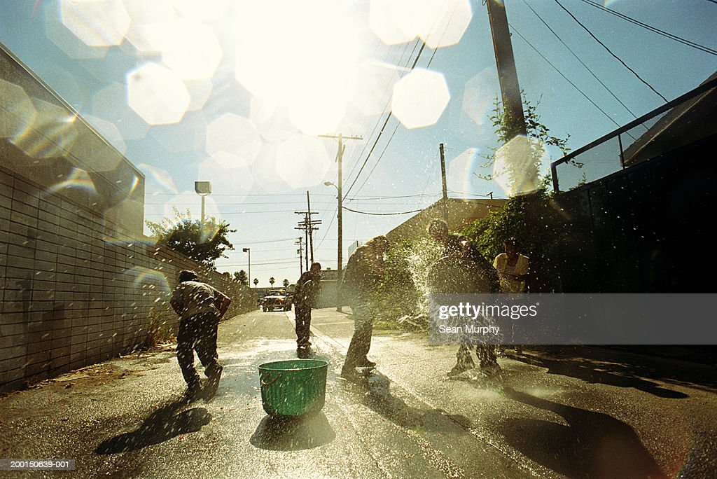 Boys (13-15) having water fight in alley : Stock Photo