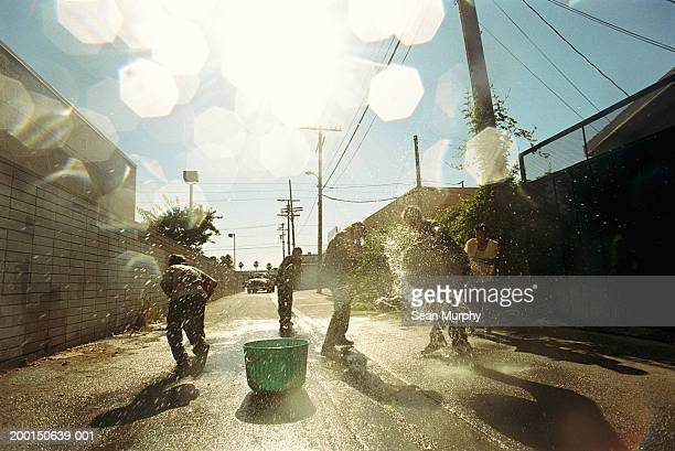 Boys (13-15) having water fight in alley