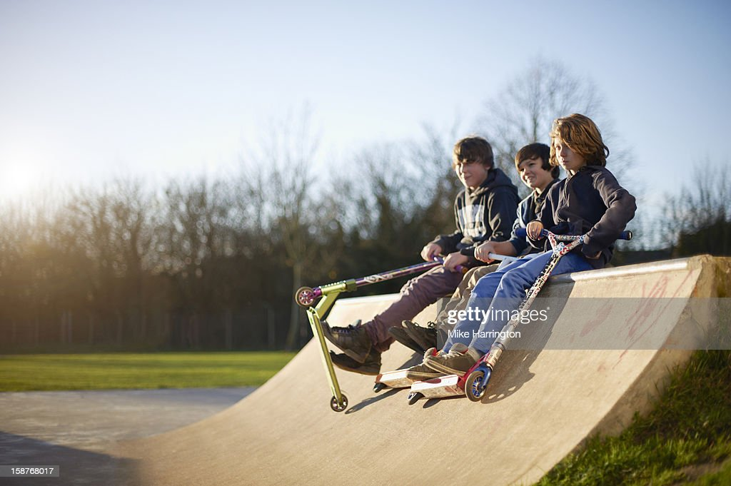 Boys holding micro scooters sitting on ramp. : Stock Photo
