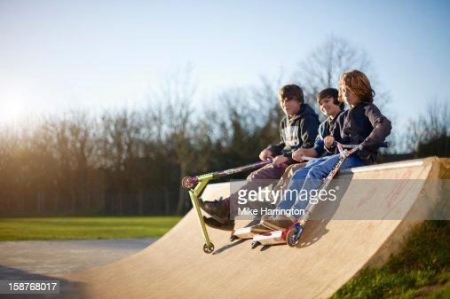 Boys holding micro scooters sitting on ramp. : Bildbanksbilder