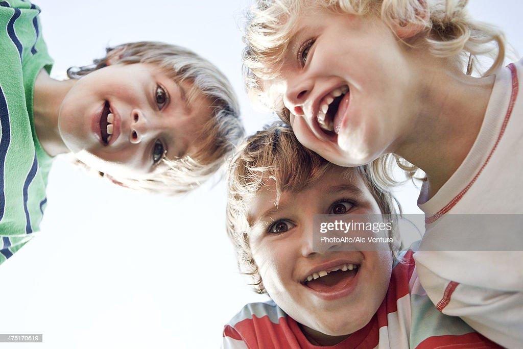 Boys huddling, smiling down at camera : Stock Photo