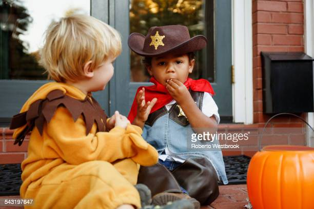 Boys in costumes eating Halloween candy