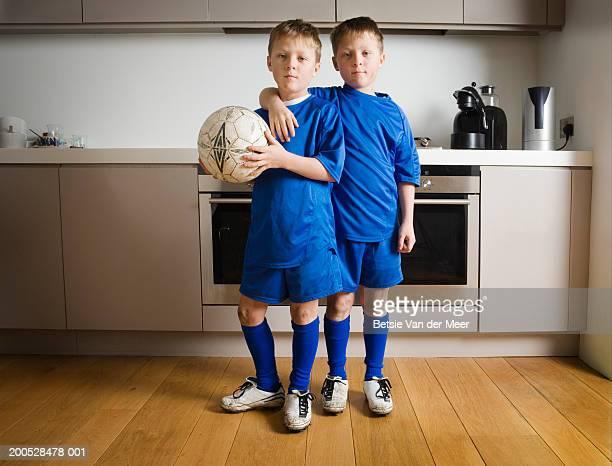 Boys (8-10) in football strip standing in kitchen, portrait