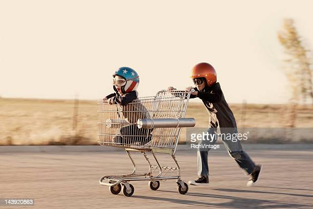 Boys in Helmets Race a Shopping Cart