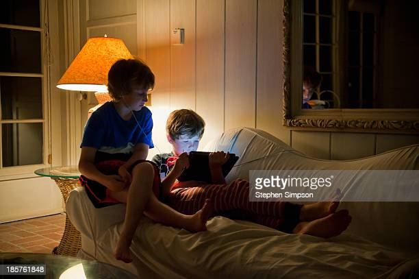 boys in pajamas sharing a tablet computer game