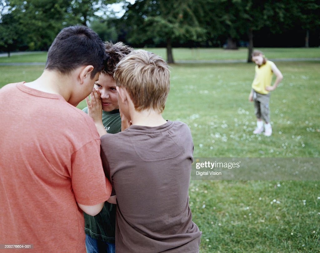 Boys (9-12) in park whispering in huddle, girl (9-11) in background : Stock Photo