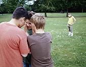 Boys (9-12) in park whispering in huddle, girl (9-11) in background