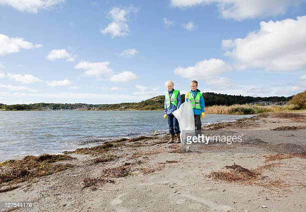 Boys in safety vests cleaning beach