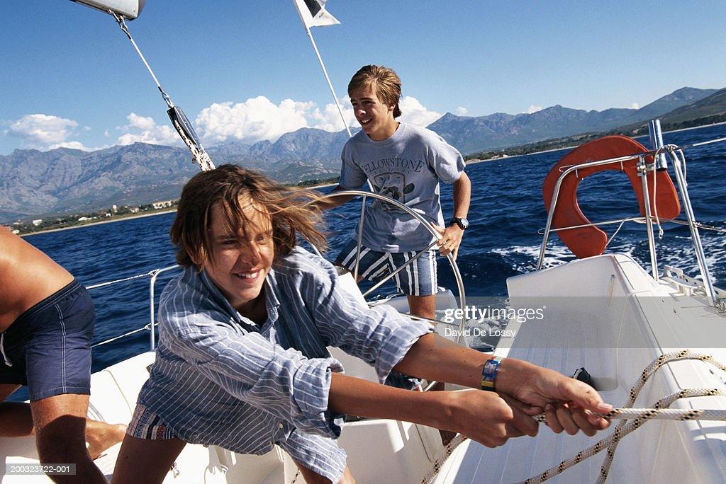 Boys (10-13) in sailboat, smiling : Stock Photo