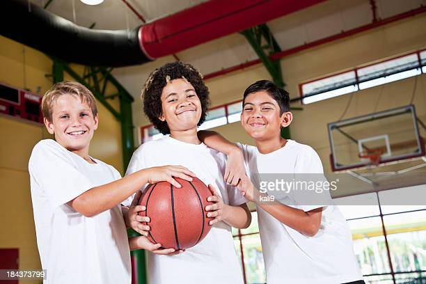 Boys in school gymnasium holding basketball