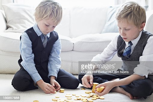 Boys in suits counting gold coins : Stock Photo