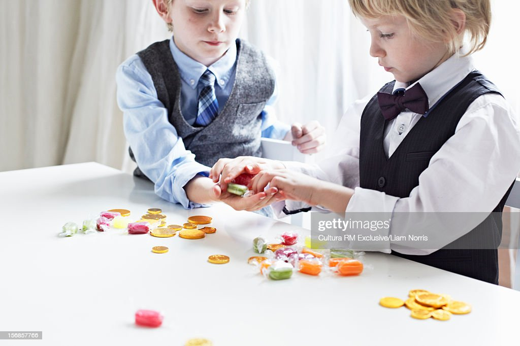 Boys in suits exchanging coins for candy : Stock Photo