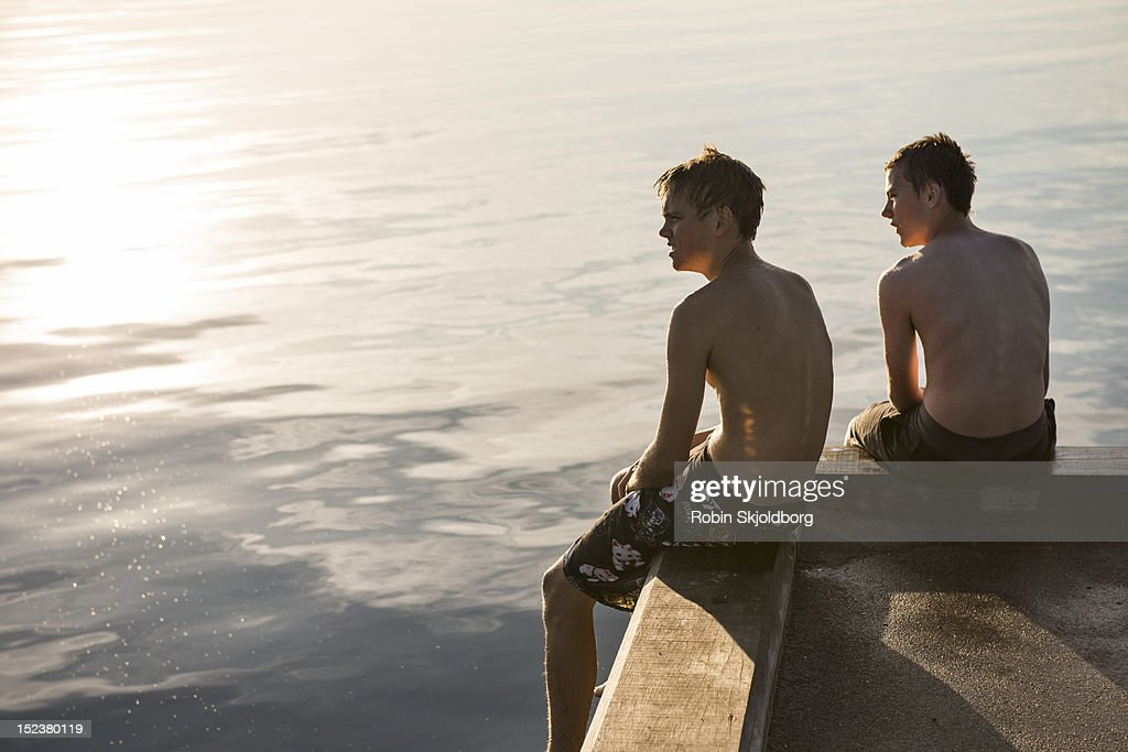 Boys in swimming trunks sitting on pier : Stock Photo