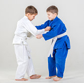 Two elementary aged boys are practicing judo fight. The cute boys dressed in sport uniforms judo gi. Studio shooting on white background