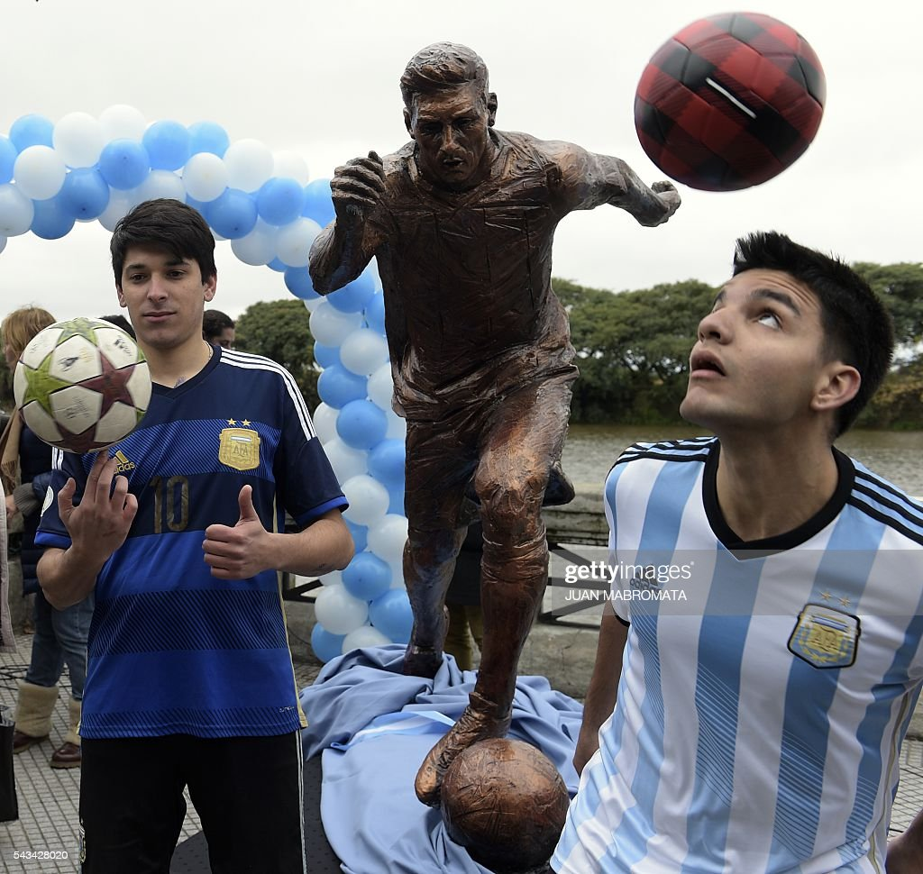 Boys juggle with footballs after a sculpture of Argentina's forward Lionel Messi was unveiled by Buenos Aires Mayor Horacio Rodriguez Larreta at the Paseo de la Gloria which pays tribute to Argentine renowned sports figures, in the South Coast promenade in Buenos Aires, on June 28, 2016. / AFP / JUAN