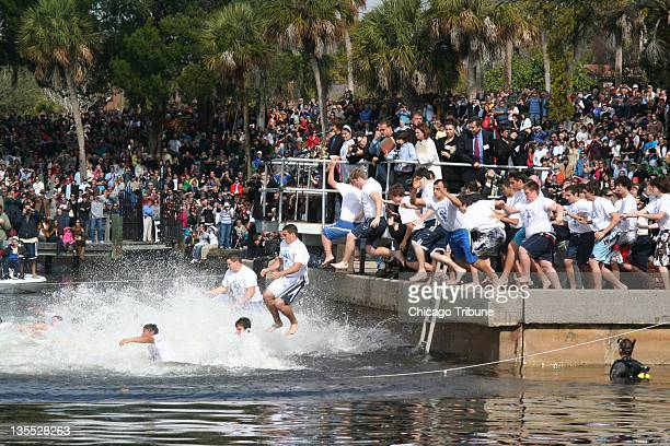 Boys jump into the water in Tarpon Springs Florida in preparation for the annual race to a crosstossed in the water on the Christian holiday of...