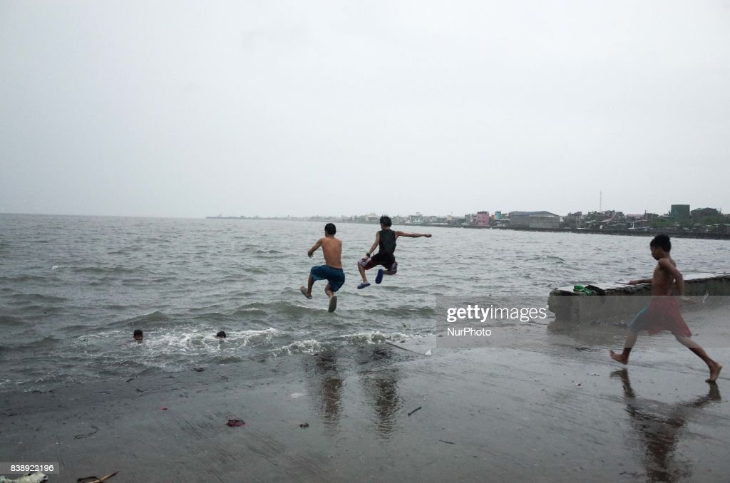 Boys jump to swim towards the Manila Bay on Friday, August 25, 2017 in Navotas City, north of Manila, Philippines. Typhoon Pakhar is set to follow the same path as Typhoon Hato, threatening Hong Kong, Taiwan, and northern Philippines with heavy rain and strong winds.