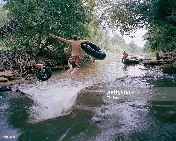 Boys jumping into river with innertubes