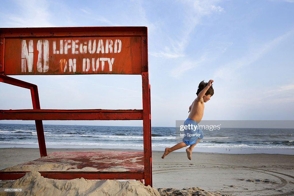 Boys jumping mid air, Long Beach, New York State, USA