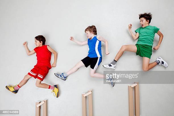 Boys jumping over hurdles
